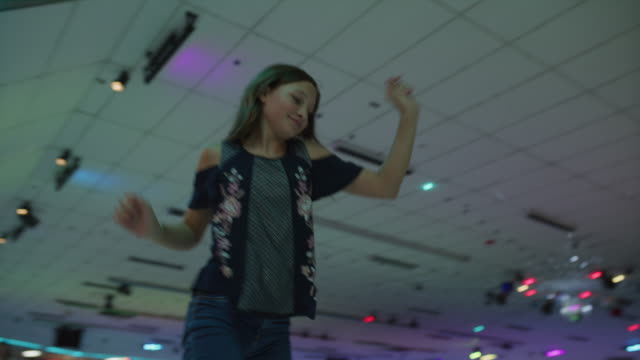 stockvideo's en b-roll-footage met slow motion tracking shot of girl skating and dancing at roller skating rink / orem, utah, united states - driekwartlengte