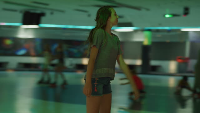 stockvideo's en b-roll-footage met slow motion tracking shot of girl skating and dancing to music in roller skating rink / orem, utah, united states - driekwartlengte