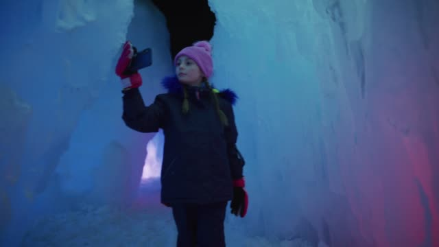 stockvideo's en b-roll-footage met slow motion tracking shot of girl walking in ice castle recording with cell phone / midway, utah, united states - exploration