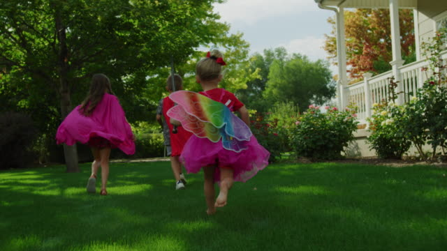 slow motion tracking shot of girls and boy running on lawn in costumes / pleasant grove, utah, united states - prato rasato video stock e b–roll