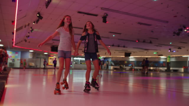 stockvideo's en b-roll-footage met slow motion tracking shot of girls skating and laughing at roller skating rink / orem, utah, united states - driekwartlengte