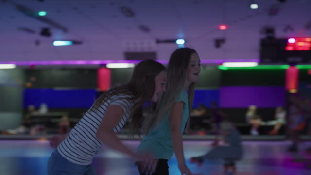 slow motion tracking shot of girls skating awkwardly at roller skating rink / orem, utah, united states - アイススケート場点の映像素材/bロール