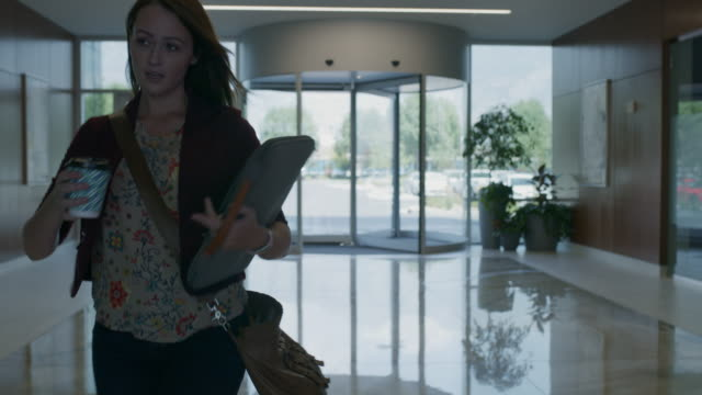 slow motion tracking shot of late businesswoman running to elevator in morning / pleasant grove, utah, united states - portare video stock e b–roll