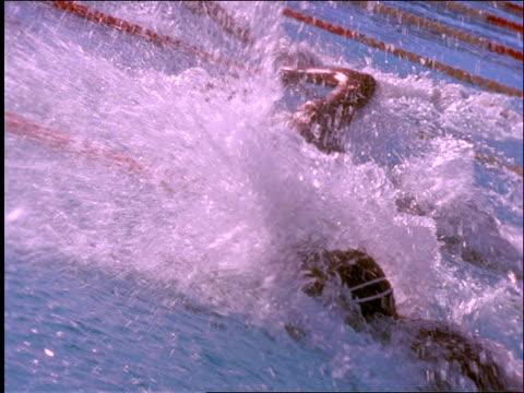 slow motion tracking shot of men swimming crawl stroke in race / splashing - freibad stock-videos und b-roll-filmmaterial