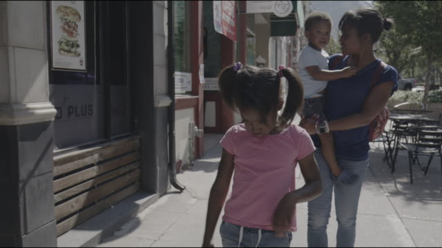 slow motion tracking shot of mother carrying son walking with daughter on city sidewalk / provo, utah, united states - provo stock-videos und b-roll-filmmaterial