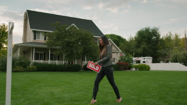 slow motion tracking shot of realtor placing sold sign on post of house for sale / pleasant grove, utah, united states - sälja bildbanksvideor och videomaterial från bakom kulisserna