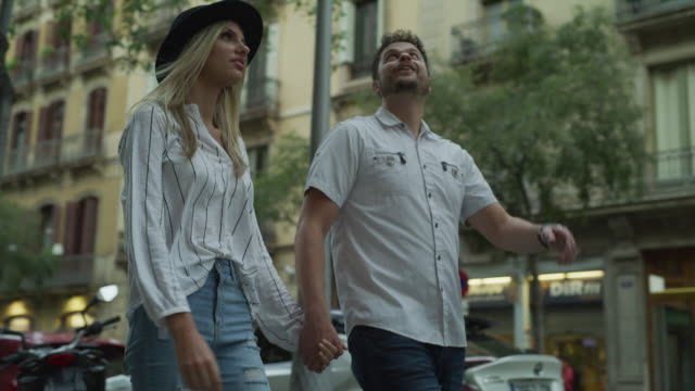 vídeos y material grabado en eventos de stock de slow motion tracking shot of sightseeing couple walking in city / barcelona, barcelona, spain - pareja joven