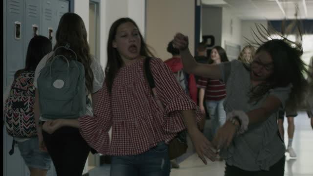 slow motion tracking shot of silly girls singing and dancing in school corridor / provo, utah, united states - aktivitäten und sport stock-videos und b-roll-filmmaterial