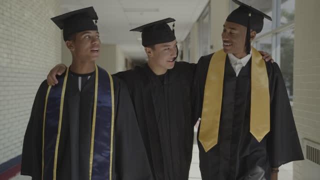 slow motion tracking shot of teenage boys graduating from high school celebrating in corridor / springville, utah, united states - ethnicity stock videos & royalty-free footage