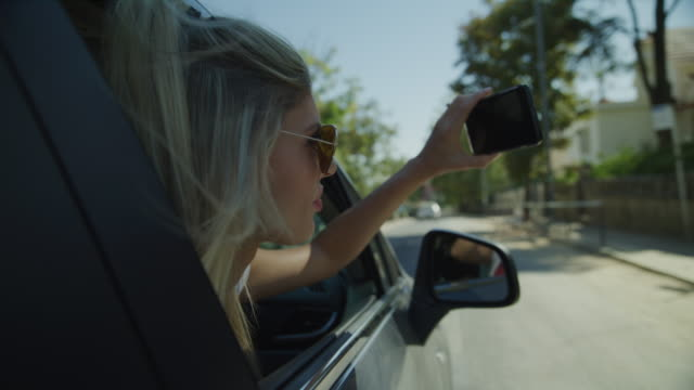 vídeos de stock, filmes e b-roll de slow motion tracking shot of woman in car photographing with cell phone / sintra, lisboa, portugal - celular com câmera