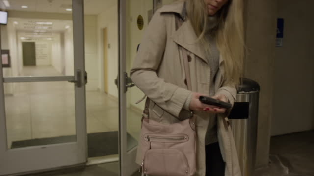 slow motion tracking shot of woman in parking garage holding gun in purse / provo, utah, united states - arma da fuoco video stock e b–roll