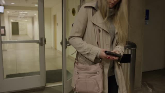 slow motion tracking shot of woman in parking garage holding gun in purse / provo, utah, united states - gun stock videos & royalty-free footage