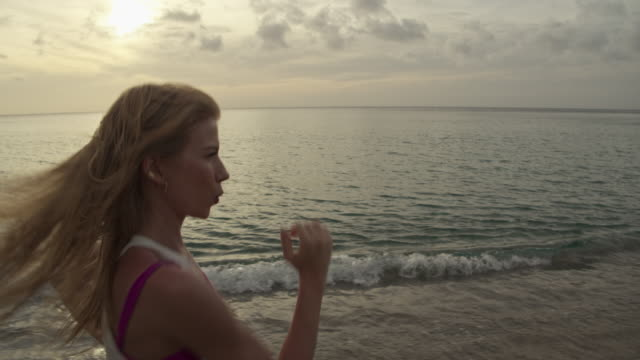 vídeos de stock, filmes e b-roll de slow motion tracking shot of woman running on beach at sunset / anse la roche bay, carriacou, grenada - plano americano