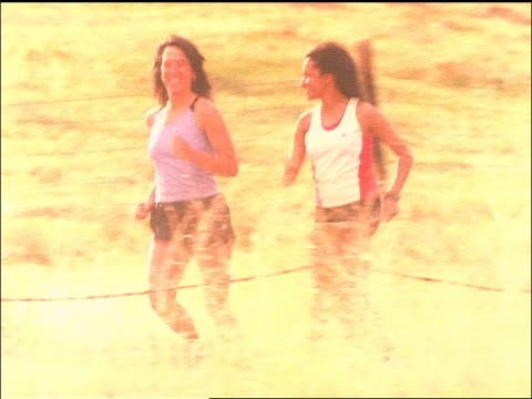 vidéos et rushes de slow motion tracking shot overexposed two women running in countryside - joggeuse