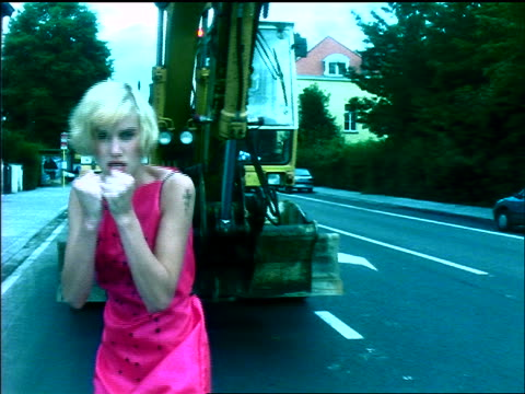 slow motion tracking shot young blonde woman with pink dress + tattoo on arm on street shadow boxing with camera