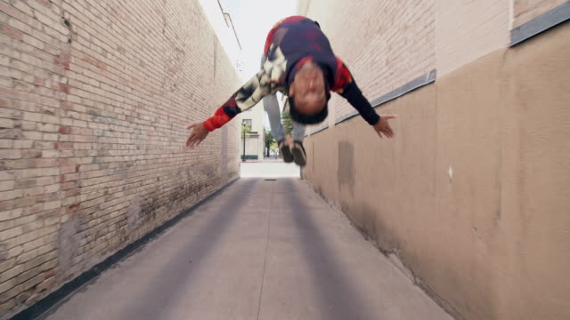 slow motion, tracking shot young man doing parkour on the street - tracking shot stock videos & royalty-free footage