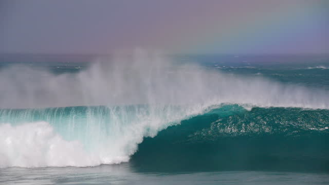 slow motion tracking surfers as they paddle over sensational giant waves with deep blue water and windblown surf - oahu, hawaii - marea video stock e b–roll