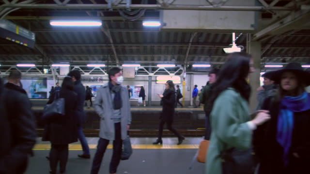 WS Slow Motion, POV of train leaving a busy station in Tokyo