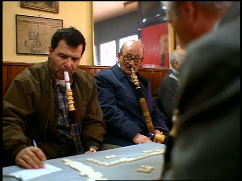 slow motion turkish men smoking large water pipes + playing dominoes at table indoors / istanbul - 薄毛点の映像素材/bロール