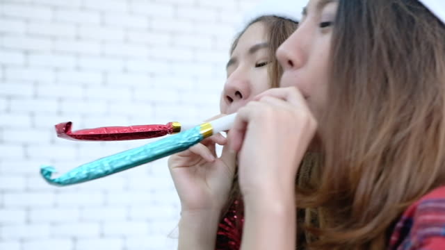 Slow motion two asian female blowing party blower forward to camera at office christmas party