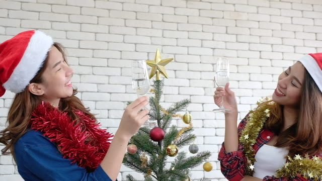 slow motion two asian female with tinsel and santa hat holding wine glass cheers together in christmas party at office.xmas holiday celebration.creative office - tinsel stock videos & royalty-free footage