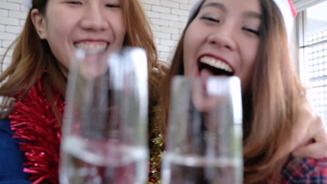 slow motion two asian female with tinsel and santa hat holding wine glass toasting together to camera in christmas party at office.xmas holiday celebration.creative office. - tinsel stock videos & royalty-free footage