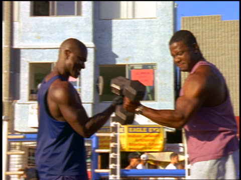 slow motion pan two black men doing biceps curls with dumbbells outdoors / muscle beach, california - arm curl stock videos and b-roll footage