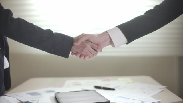 slow motion two businesswoman partners shaking hands on profitable agreement - ambassador stock videos & royalty-free footage