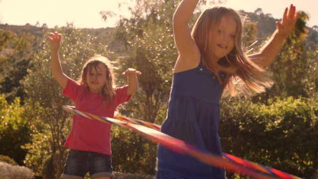 slow motion two children playing with hula hoop in park. - plastic hoop stock videos & royalty-free footage