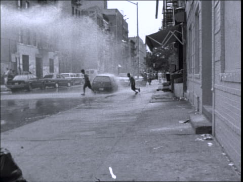 b/w slow motion pan two children running across street in spray of open fire hydrant / nyc - fire hydrant stock videos & royalty-free footage