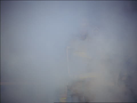 slow motion ms two firefighters running through smoke carrying ladder - solo uomini di età media video stock e b–roll
