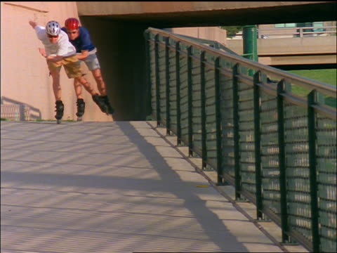 slow motion two male inline skaters wearing sunglasses + helmets coming towards camera / Denver, Colorado