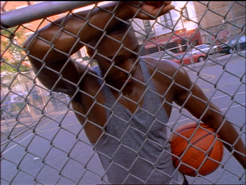 slow motion PAN two men (1 Black) resting against fence + sharing water after playing basketball / NYC