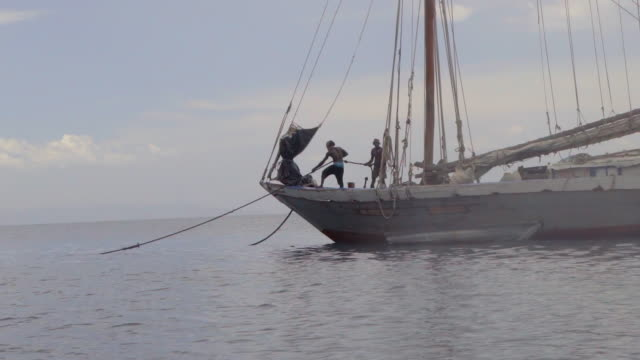 slow motion: two men standing on sailing boat pulling in anchor - schiffsmast stock-videos und b-roll-filmmaterial