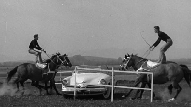 b/w 1954 slow motion two men standing + riding on horses jump simultaneously past each other over car - 1954 stock videos & royalty-free footage