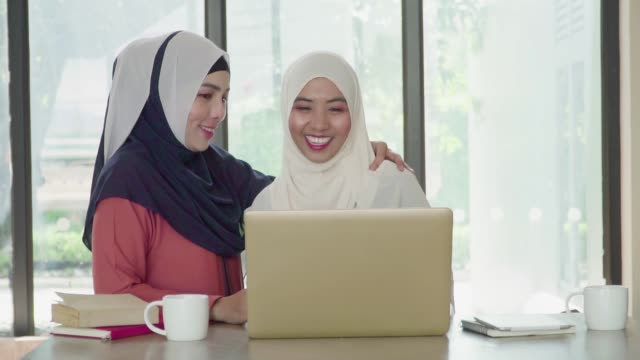 slow motion: two muslim people working and discussion with laptop at working space. - kufi stock videos & royalty-free footage