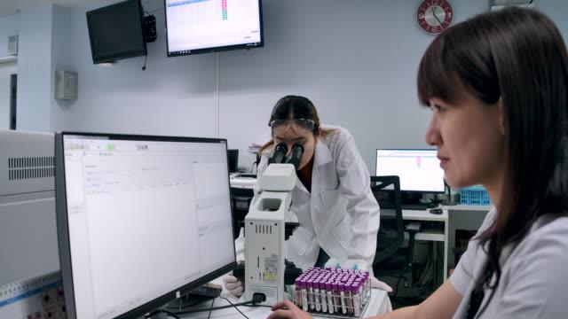 4k zeitlupe zwei wissenschaftler gehen zu fuß sprechen über forschung studie zusammenfassung im labor - physik stock-videos und b-roll-filmmaterial