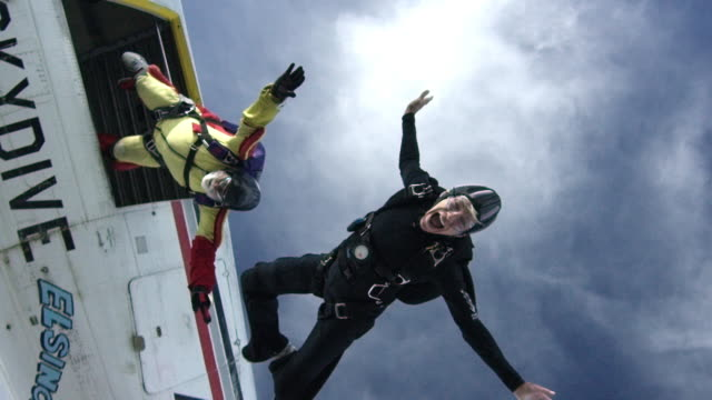 vidéos et rushes de slow motion - two senior skydivers exit airplane - parachute