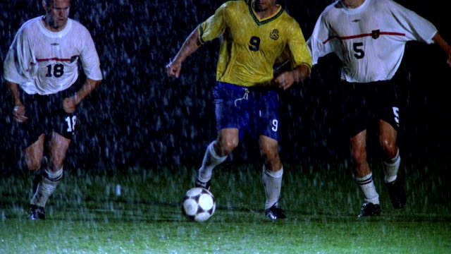 slow motion MS two soccer players sliding with feet to take ball from opposing player in rain at night