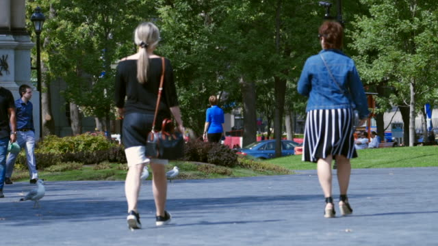 slow motion: two women walking away across square in montreal - fußgänger stock-videos und b-roll-filmmaterial