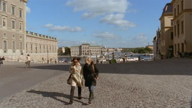 Slow motion two women walking towards camera / Stockholm, Sweden