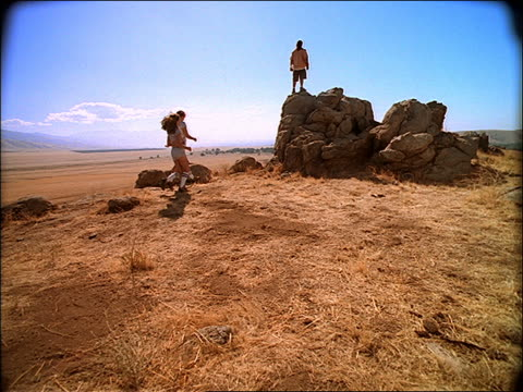 slow motion two young Generation X women running + three men walking to rocks with man on top
