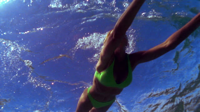 slow motion underwater low angle pan woman swimming + surfacing for air / fiji - fiji stock videos & royalty-free footage