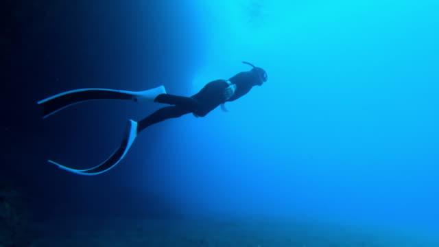 vidéos et rushes de tir sous-marin au ralenti d'un plongeur nageant hors d'une grotte - plongée sous marine autonome