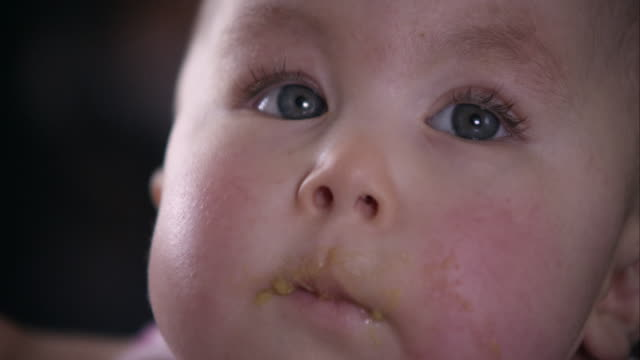 Slow motion up close of baby girl being spoon fed.