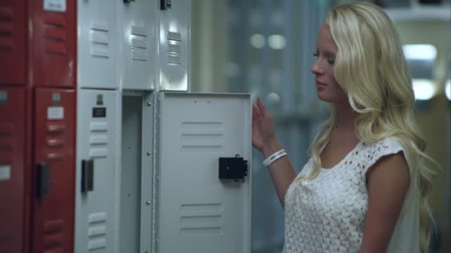 vídeos de stock e filmes b-roll de slow motion upward pan of teenage girl missing part of left arm at her locker. - braço humano