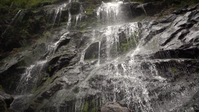 slow-motion blick des wasserfalls auf felsigen klippen nach oben - einfachheit stock-videos und b-roll-filmmaterial