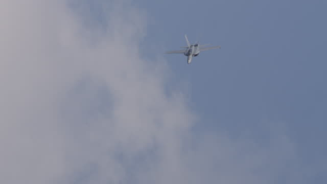 slow motion us f-18 hornet military air force fighter jet loops in the sky. - fighter stock videos & royalty-free footage