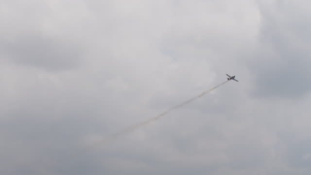 Slow motion US P-51 Mustang military prop fighter plane and vintage Japanese A6M Zero military fighter plane flies over military base at an air show.