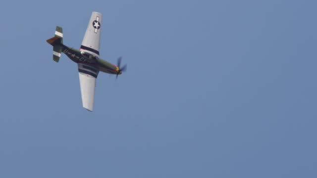 Slow motion US P-51 Mustang military prop fighter plane flies overhead.